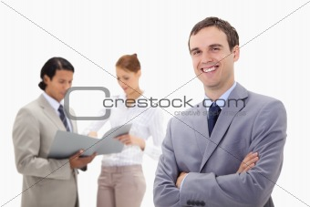Smiling young businessman with talking colleagues behind him