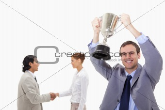 Businessman raising cup with hand shaking colleagues behind him