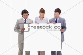 Businessteam looking at blank sign in their hands