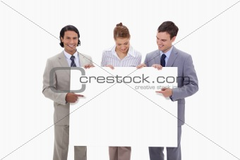 Businessteam pointing at blank sign in their hands