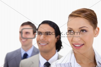 Smiling businessteam standing in a row looking right