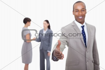 Smiling businessman offering his hand with hand shaking colleagues behind him