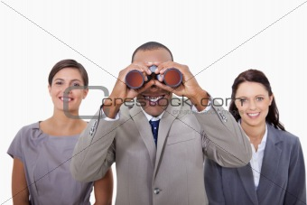 Businessman with colleagues looking through binoculars