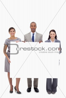 Businesspeople holding blank sign