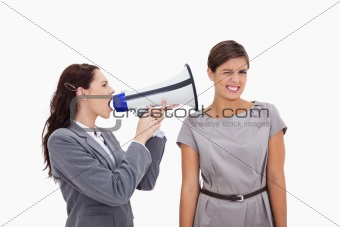 Businesswoman with megaphone yelling at colleague