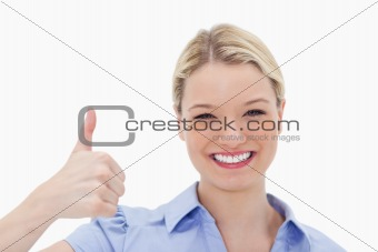 Smiling woman giving thumb up