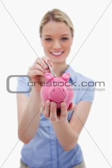 Note being put into piggy bank by woman