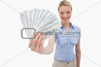 Money being held by smiling woman
