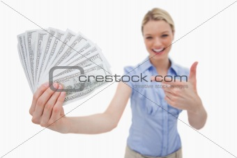Money being held and pointed at by woman