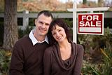 Happy Attractive Caucasian Couple in Front of Real Estate Sign.