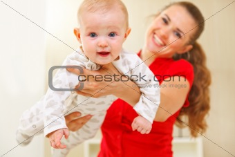 Happy mother and lovely baby playing on divan