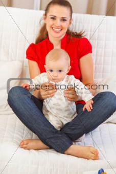 Adorable baby sitting on mothers laps