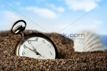 Old pocket watch buried in sand