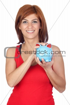 Beautiful redhead girl with a blue piggy-bank