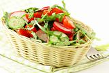 salad with arugula and cherry tomatoes on a wooden plate