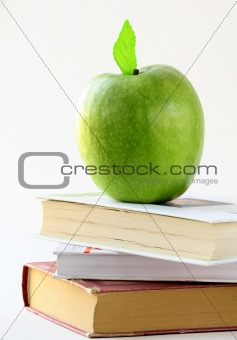 Three books and apple on the desk, on white