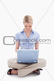 Smiling sitting woman working on her laptop