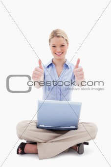 Sitting woman with laptop giving thumbs up