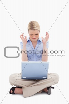 Woman sitting and angry about her laptop