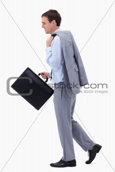 Side view of walking and smiling businessman with suitcase