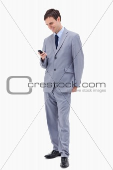Smiling businessman reading text message