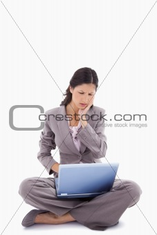 Sitting woman having trouble with laptop