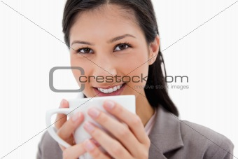 Smiling businesswoman holding cup close