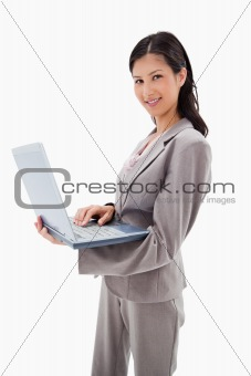 Side view of smiling businesswoman standing with laptop