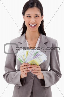 Smiling businesswoman with bank notes in her hands