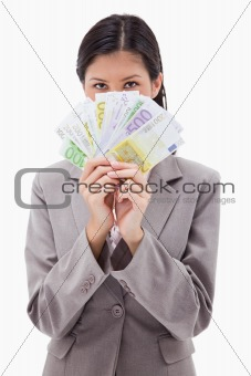 Businesswoman hiding face behind money