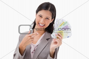 Smiling businesswoman pointing at her money
