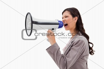 Side view of angry businesswoman shouting through megaphone