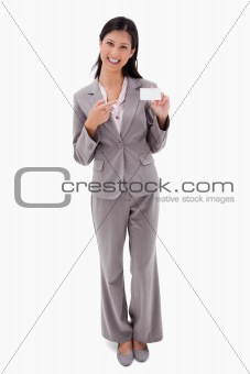 Smiling businesswoman pointing at blank name bagde