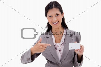 Smiling businesswoman pointing at blank business card