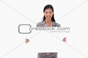 Smiling businesswoman with blank sign board