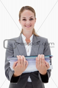 Smiling office employee with a pile of paperwork