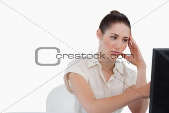 Tired businesswoman using a monitor
