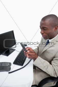 Portrait of an angry businessman talking to the phone while using a monitor