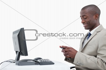Side view of a smiling businessman sending a text message