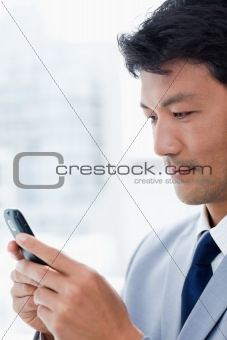 Portrait of an office worker using his mobile phone