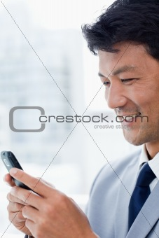 Portrait of a smiling office worker using his mobile phone