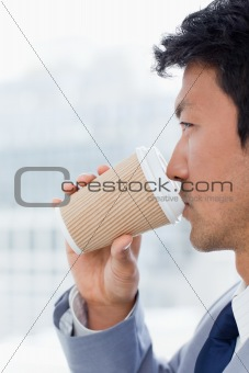 Portrait of an office worker drinking a takeaway coffee