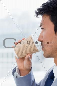 Portrait of an office worker drinking a takeaway coffee