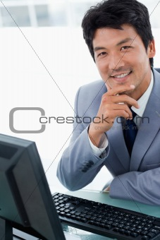Portrait of a happy manager using a computer