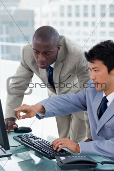 Portrait of an office worker showing something to his colleague