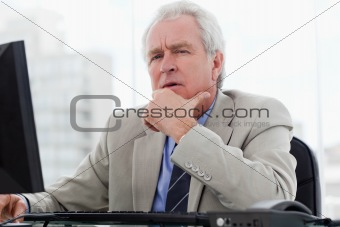 Thoughtful senior manager working with a monitor