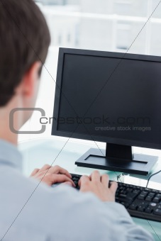 Back view of a businessman using a monitor