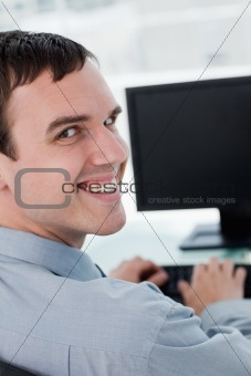Back view of a young businessman using a monitor