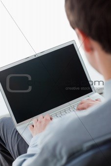 Back view of a businessman typing on a laptop