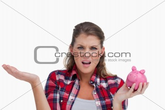 Broke woman holding a piggy bank